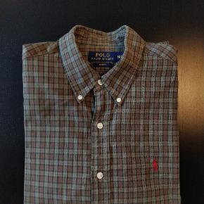 Lækker Oxford skjorte fra Polo Ralph Lauren i brun/grå/rød tern og rødt logo broderet på brystet. Modellen er slimfit, medium og sidder tæt til kroppen. Brugt en håndfuld gange, men helt uden slid eller skader. Der medfølger ekstra knapper.