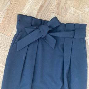 Smuk nederdel i sort! Den ser blå ud men den er helt sort. Bælte kan tages af og der er en kort slids bagpå