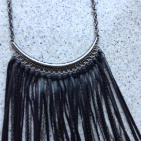 Varetype: Halskæde Størrelse: 20 cm lange frynser Farve: Sort Oprindelig købspris: 200 kr.  Super rock'et halskæde med kæder og læderstrimler. Flot til en enkel buksedragt eller andet med dyb udskæring