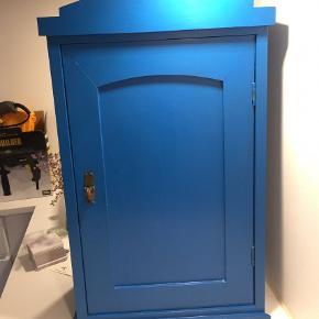 Vægskab, Hængeskab, Lille skab  Smukt gammelt træskab som jeg selv har malet blåt.  Mulighed for at hænge op på en væg  Måler 39 cm lang 63,5 høj og 21,5 dyb  Mangler lille træstykke nederst på højre side (kan ses på billedet)  Byd gerne