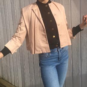 Yndig kort blazer i sart pudderrosa - smuk til fest med pailietter og glimmer eller til en dejlig aften med klassisk hvid t-shirt og jeans. Giver en flot figur.   Kom gerne med et forårsbud.
