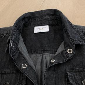 Fin skjorte fra The New. Kan bruges af både piger og drenge. Den har trykknapper og med vasket look. Mørkegrå / lysere grå