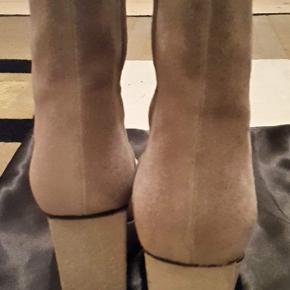 Flotte støvletter af ruskind med 3 cm plateau og 8 cm kilehæl. Smart design og behagelige både til hverdag og fest. Skoene er lige som nye i original æske og med støvpose. Købspris 3600 kr.