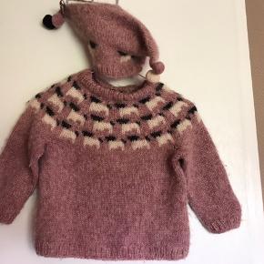 Hjemmestrik/ Uldtrøje i 100% uld, mega sød med lammemotiv og matchende hue med pompom Har været brugt som str. 3-4 år