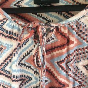 Tunika i storpige small i blødt viskose-stræk materiale.  Ærmer i 3/4 længde, afsluttet med elastik i kanten. 92% viskose, 8% elastan