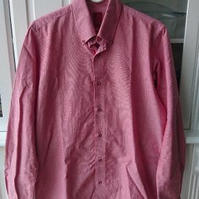 Flot rød skjorte med fede detaljer. Farven er som på billederne, hvor den hænger på bøjle. Størrelse L eller 41/42.