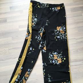 Sorte blomster bukser, med en gul streg i siden. aldrig blevet brugt, str. M