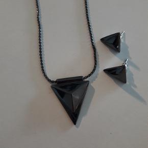 Ubrugt hæmatit-farvet smykkesæt fra Pilgrim. Smykkesættet opbevares i lufttætpose og fejler intet. Længste længde på kæden er ca. 47 cm.