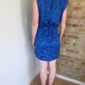 Smuk smuk blå jarquard-vævet kjole med de flotteste asymetriske detaljer. Fejler absolut intet. Nypris: 3800kr. Sælges for 975kr!