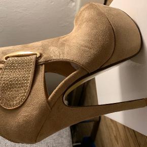 Helt nye og ubrugte stilletter i en str. 36. Hælen er 15 cm og plateau 4 cm.