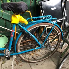 Mangler du en skøn damecykel, som du altid kan finde? Så sælger jeg min gamle cykel. Den er købt for 3 år siden, har slid, men kører stadigvæk godt. Der er 7 gear (nr 5 hopper lidt, men kan fixes hvis nødvendigt).  Der er kommet nyt bagdæk på samt skiftet et en punkterfri slange. Hjulene trænger dog til at blive pumpet. Der er sat en cykelkurv på, men den kan fjernes. Revne i saddel (derfor pose over, men sådan fungerer det fint - kan evt gøres lidt pænere).  Nøgle til lås medfølger.   Skal afhentes i Aarhus C.   Sælges billigt, så kom gerne med bud.