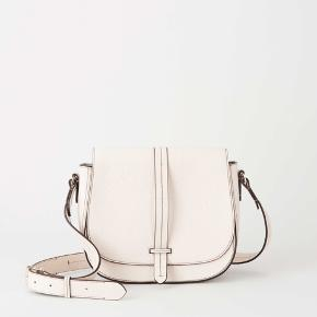 Saddle bag in grainy leather with contrast stitching Flap with strap closure Adjustable shoulder strap with branded hardware Open pocket at back Inside features one open pocket and one zipped pocket Size: 20 x 26 x 9 cm