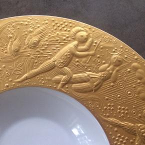 """Smuk hvid porcelænstallerken med guldkant dekoreret med motiv fra """"tryllefløjten"""". Designet af Bjørn Wiinblad for Rosenthal. Tallerknen kaldes for grøntsags bowl, og kan stadig købes online hos Rosenthal for 5700,-kr. Fremstår som ganske ny, ingen ridser, skår eller skrammer... pris + porto(DAO).... gerne mobilpay eller TS-handel +5%"""