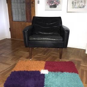 Fint lille hjemmeknyttet rya tæppe / måtte / forligger. Lilla, orange/cognac, turkis, mørkerød og off white colour block. Trådene er ikke klippet til, så de er lidt uens i længden. Uld. Ikke slidt.  Længde 92 cm, bredde 66 cm.