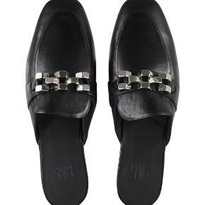 Flotte slippers I sort læder med sølvspænde.