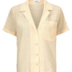Klassisk skjorte i tern. Carolina shirt har korte ærmer og en bred krave, som ender ud i en dyb v-udskæring. Skjorten er i en lækker viskose kvalitet. 80% Rayon, 20% Nylon. Aldrig brugt