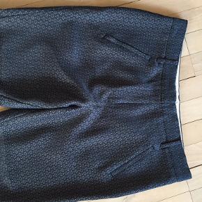 Bukser i bundfarven mørkeblå med mønster. Farven hedder. Navy blush. Modellen hedder. Angelie split. Lomme med lynlås i hver side, pyntelommer bagpå. Livvidde: 86 cm, Indvendig benlængde: 65 cm, udvendig benlængde: 91 cm. Kun brugt enkelte gange, fejler intet!