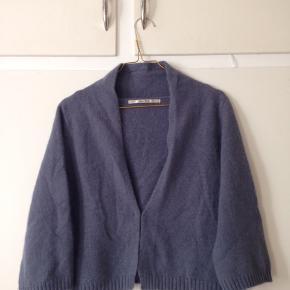 Lækker kort cardigan med 3/4 ærmer i den fineste blågrå farve. Lukkes med en hægte foran.