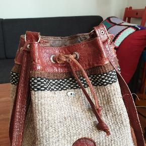 Retro skuldertaske i læder. Farven i læderet er en rustrød farve.  Stoffet er en uldblanding.
