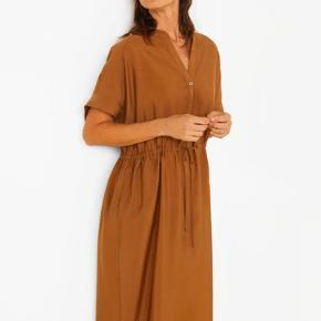 Fin og let kjole fra Mango i brunlig farve med lommer og snøre i livet. Materiale: 85% lyocell, 15% polyester. Kjolen er løstsiddende. Brugt og vasket én gang, men der er desværre kommet en plet (se billede) - mistænker det er vaskemiddel. Nypris: 449 kr.
