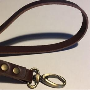 Læder keyhanger/ nøglering med Karabinhage og ekstra nøglering.   Solid keyhanger i kernelæder. Den er 12 mm bred og passer perfekt til arbejdsnøgler mm  Keyhangeren måler ialt ca 47 cm og laves i farverne: - natur - Mørkebrun - Cognac - Sort  Karabinhage og nøglering fås i farverne: - Metal - Gammel messing  Kombiner selv din favorit, til en personlig gave, til dig selv eller en du holder af.  Da læder er et natur materiale, hvor ikke to stykker er ens og fordi alle nøgleringe/ keyhanger er håndlavede, kan de derfor variere i udtryk.
