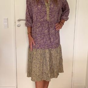 Sissel Edelbo kjole Model: Bounty dress kjole  Størrelse: S/M Farve: Multifarvet støvet lilla lysegul mm Købspris: 999,-   Super flot kjole fra Sissel Edelbo Ny og stadigvæk med prismærke. Super blød og utrolig lækker❤️  Utrolig smuk kjole fra Sissel Edelbo. Denne Bounty kjole med smukke detaljer bliver helt klart din nye favorit! Det er super let at style både oven på et par jeans eller med bare ben og en tyk strik. Den er oz perfekt stylet med et bredt bælte i taljen for at give mere facon og silhouet. De draperede lag giver et boheme og afslappet look til kjolen. Kjolen har en V-hals med knapskaft samt på ærmerne. Denne kjole er perfekt til enhver lejlighed - især hvis du vil se festlig ud, men alligevel føle dig super behagelig og afslappet.   Til denne kjole er der opcyklet flere saris. Alle sarier er håndplukkede af Sissel Edelbo, og er, før de blev re-designet, blevet båret af en indisk kvinde, som en saree pakket rundt om hendes krop. Hendes ånd er stadig i dette stykke stof. Kvindens og sariens historie viser sig i de unikke mønstre og små karakteristika. Ved at bære er stykke tøj fra Sissel Edelbo fortæller du historien videre.  Da stoffet er genanvendt, kender vi ikke den totale sammensætning af stoffet, som er håndplukket i Indien som en silke-mix. Der kan af samme grund forekomme små fejl i stoffet. De små fejl er en del af sariens charme og historie og betragtes ikke som en reklamation.  Alle produkter fra Sissel Edelbo er unikke.  Dvs der kun findes den ene du ser her på billedet og kun i den viste størrelse.  Dét gør din kjole helt unik - og et smukt og farverigt alternativ til andre kjoler.   LET THE STORY CONTINUE 💞  FROM ONE WOMAN TO ANOTHER