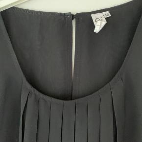 Que top med let plissé og undertop, så den ikke er gennemsigtig. 100% polyester - rund hals og lille ærme.