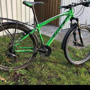 """Mountainbike med 21 gearRockmachine Manhatten 40 Stelnummer : RM1529211K  27"""" hjul  Ny pris 4050 kr. Købt hos Design Cykler den 09-09-2015. Passer til en 11-15 årig. Service aftale overholdt. Med bagagebærer, skærme, nyere lås og støttefod. Gear i bag trænger til service af ny ejer. Sælges da min søn er vokset fra cyklen. Cyklen er 3 1/2 år gamnel og naturligvis brugt med små fejl"""