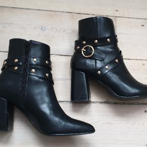 Sorte højhælede støvler med metal detaljer og i læder look med metal detaljer på, super fede De er str 38   De har været brugt et par gange, har lidt skader ved hæl og ridser, se billederne Det ses ikke rigtigt når man har dem på  de sælges for 250kr de kan sendes med DAO for 38kr