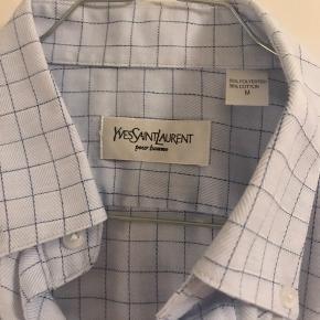"""Lækker Yves Saint Laurent skjorte købt i en vintage butik i Paris. Skjorten er sat som """"god men brugt"""", da den er vintage - men den er stadig i super fin stand og har mange flotte detaljer. Bl.a. på knapperne. Skjorten er oprindeligt en herreskjorte, men jeg har brugt den som oversize skjorte. Mit bud er at den svarer til en str. 40-42 i kvindestørrelse.  Se også mine andre annoncer🍁🍂🍊"""