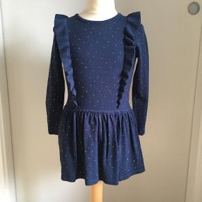 Flot mørkeblå kjole med flæser og guldprikker. Brugt meget få gange og fremstår som ny.