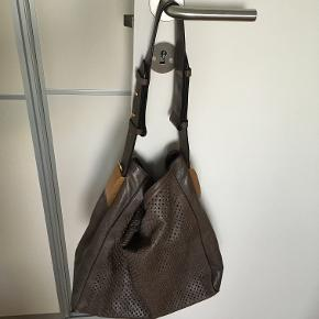 Elegant and simple shoulder bag in beige/light brown. Very airy (it has small holes all over. Coming with one shoulder strap (lengths seen on the pics) and has removable pocket/wallet inside. Closes with one magnet. More inform on request.