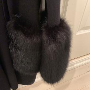 Strikket frakke med fake pelskant på ærmer og lommer. Aldrig brugt.