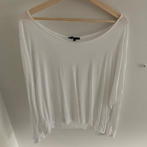 Fin tynd bluse med lange ærmer, stor hals og huller i ryggen.