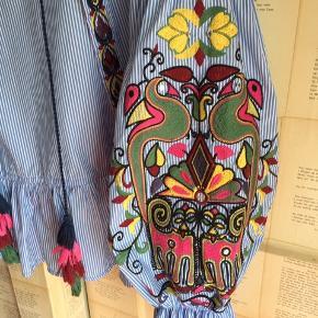 Stribet skjorte med broderi / brokade og mange fine detaljer og kvaster. Ærmer med vidde.   Er aldrig brugt.  Nypris 799.