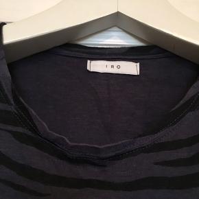 Fin t-shirt fra franske IRO i 100% bomuld. Brugt , men uden huller, pletter, eller lign. Minimalt fnuller i overfladen hist og pist hvis man kigger helt tæt på (ikke iøjnefaldende). Har drejet sig lidt til den ene side efter vask. Har klippet str, ud, men husker den som en 38. Tjek mål for en sikkerhedsskyld. Brystmål: 48 cm på tværs fra armhule til armhule + strech, dvs 96 cm i omkreds+ strech. Længde: 53 cm fra nakken og ned. Søgeord: T-shirt bluse bomuld mørkeblå navy sort stribet Tiger striber zebra top kort