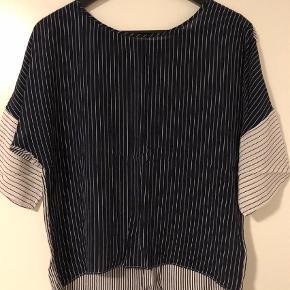 Varetype: T-shirt Farve: Blå Prisen angivet er inklusiv forsendelse.  Med 3 forskellige slags striber i blå og hvid - mørkeblå med hvid stribe på fronten, hvid med blå stribe på ærmerne, og hvid og blå stribet bagpå. Materialet er 100 % silke. Oversize ærmer.