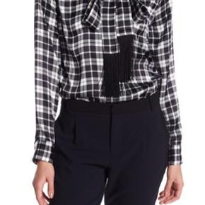 Bluse med bindebånd i halsen. Kan styles lukket eller åben. 100% silke.   NP: 1700,-