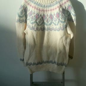 Uldsweater i råhvid med smukt lyserødt og lyseblåt mønster og brede ribstrikkede kanter forneden og ved ærmegab. Kun brugt få gange. Håndstrikket, super kvalitet, 100 % uld, fremstillet i Danmark 🇩🇰