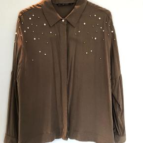 Varetype: Langærmet Farve: Armygrøn  Grøn/brun skjorte med perler. Kan sendes mod betaling af porto kr. 40,00 med DAO.