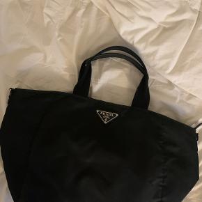 Jeg sælger min Prada skuldertaske i sort, som har absolut ingen tegn på slid. Der kan være Macbook i tasken. Min mindste pris ligger på 2000 kr, men du er velkommen til at give et bud!