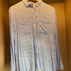 Fin skjorte med lyseblå/hvide striber. Næsten strygefri. 100% viskose.