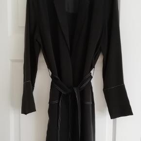Bytter ikke!  Eksklusiv porto.   Jeg har købt denne smukke jakke - kjole -kimono, privat, på nettet, men har ikke fået den i brug.  Den er fra Kokoon str. M i sort 100 % 100% sort silke, med creme/hvide stikninger. 2 paspolerede lommer, bindebånd som lukning.  Størrelsesguide str. M: Bryst mål 92 cm Talje mål 76 cm Hofte mål 102 cm. Længde fra nakken og ned 110 cm. Modellen på billederne er str. M/L. Bryst mål 92 cm, hofte mål 102 cm.   Kommer fra et ikke ryger hjem. Hænger i dragtpose.