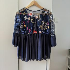 Chiffon top with embroidered flowers on the back.