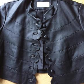 Kort blød PU jakke med fine knap detaljer. Kun brugt 2 gange og nu har den hængt længe nok i mit skab. Længde 42. Bryst 46x2  Kig forbi mine andre annoncer 😊 Altid mængderabat  Kort PU  jakke med 3/4 ærmer Farve: Sort