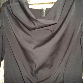Varetype: tunika Farve: sort  Smuk tunika med en vandfalds udskæring rynkede ærmer og en flot synlig lynlås bagpå