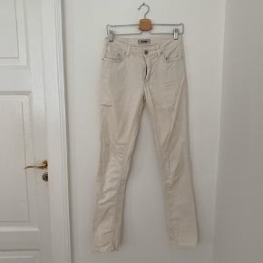 Råhvide bukser fra Acne. Hul ved to af bæltestropperne - det kan ikke ses når buksen sidder på og kan alternativt syes