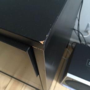 Ikea Trollsta skænk i sort sælges.  Designet af Hanna Brogård  B: 183 D:50 h:76  Nypris: 2199kr  Da skænken har fået nogle slag ved sidste flytning sælges det derfor til den billige pris! (Se billeder). Udover dette er skænken fin.   Det kan hentes i Vanløse og køber skal selv bære det ned fra 1. Sal. Det er et tungt møbel! - så der skal være flere om at bære det. Det er muligvis lettere hvis det bliver skilt lidt ad.