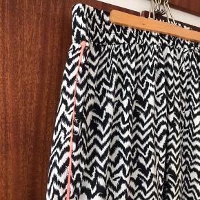 Flotte bukser i let stof og med fed kontrastfarve langs siden. Fin stand
