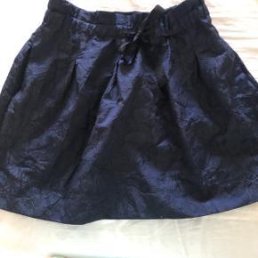 Sød nederdel med mønster, ubrugt. Med sort bindebånd